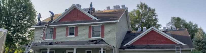 Roofing and Siding Contractors work on repairing hailstorm damage on roof.